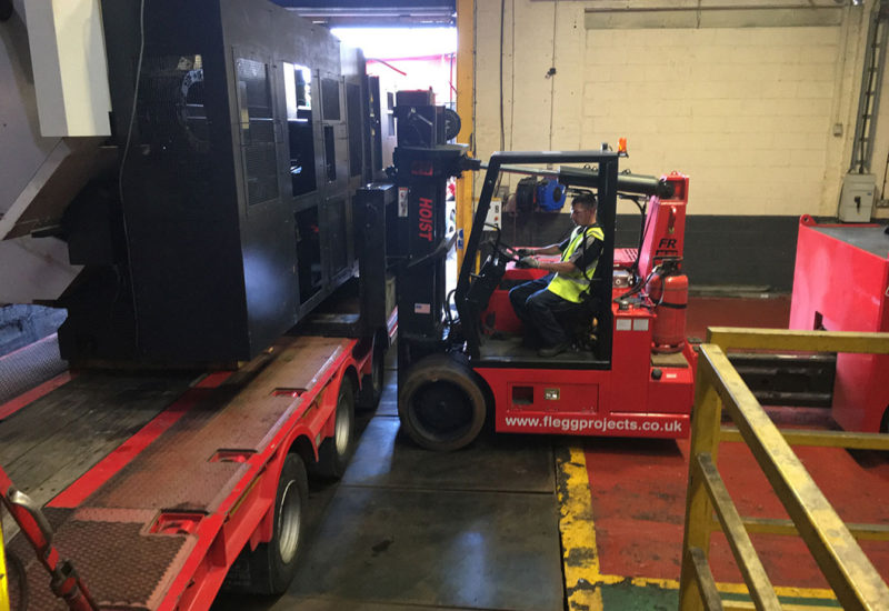 forklift loading a truck with machinery